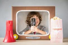 Kind, das mit Karikatur Fernsehen spielt Lizenzfreie Stockfotografie