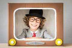 Kind, das mit Karikatur Fernsehen spielt Stockfotografie
