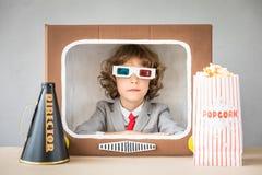 Kind, das mit Karikatur Fernsehen spielt Stockfotos
