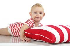 Kind, das mit Kissen liegt Stockfotografie