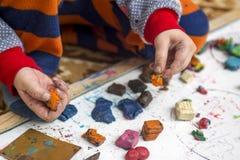 Kind, das mit Lehm spielt Kinderspiele mit Plasticine in einem Kindergarten oder zu Hause stockbilder