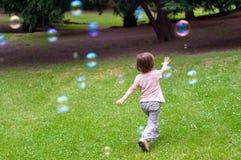 Kind, das mit Luftblasen spielt Stockfotos