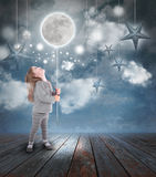 Kind, das mit Mond und Sternen nachts spielt Lizenzfreie Stockfotos