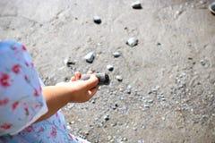 Kind, das mit Rock auf dem Strand spielt Lizenzfreie Stockfotos