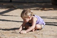 Kind, das mit Sand auf dem Spielplatz spielt Lizenzfreie Stockfotos