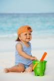 Kind, das mit Sand auf dem Strand spielt Stockbild