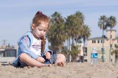 Kind, das mit Sand auf einem Strand spielt Stockbild