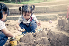 Kind, das mit Sand im Spielplatz spielt lizenzfreie stockfotografie
