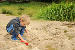 Kind, das mit Sand spielt Lizenzfreies Stockfoto