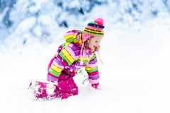 Kind, das mit Schnee im Winter spielt Kinder draußen stockbilder