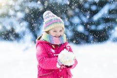 Kind, das mit Schnee im Winter spielt Kinder draußen Stockfotografie