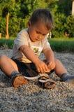 Kind, das mit Schuhen spielt Stockfoto