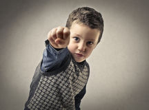 Kind, das mit seiner Faust zeigt stockbild