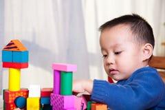 Kind, das mit Spielzeugblöcken spielt Stockbild
