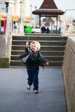 Kind, das mit Spielzeugwindmühle läuft Lizenzfreie Stockbilder