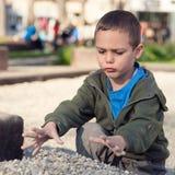 Kind, das mit Steinen im Park spielt Stockfotos