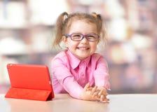 Kind, das mit Tablet-Computer sitzt stockfotos
