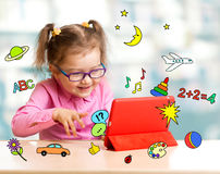 Kind, das mit Tablet-Computer sitzt und wi lernt stockbild