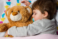 Kind, das mit Teddybären schläft Lizenzfreies Stockfoto