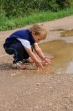 Kind, das mit Wasser spielt Stockfotos