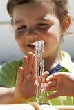 Kind, das mit Wasser spielt Lizenzfreie Stockfotografie