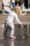Kind, das mit Wasser spielt Stockfotografie