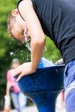 Kind, das mit Wasser von einem Straßenhahn kühlt lizenzfreie stockfotografie