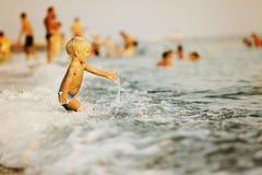 Kind, das mit Welle im Meer plaing ist Lizenzfreie Stockbilder