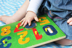 Kind, das mit Zahlpuzzlespiel spielt Lizenzfreies Stockfoto
