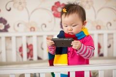 Kind, das Mobiltelefon spielt Stockfotografie