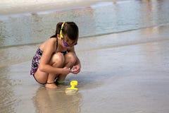 Kind, das nach Oberteilen am Strand sucht. Stockfotos