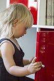 Kind, das nach Schokolade im Schrank sucht stockbild