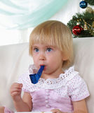 Kind, das nahe zum Weihnachtenc$pelzbaum spielt Lizenzfreies Stockfoto