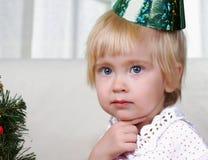 Kind, das nahe zum Weihnachtenc$pelzbaum spielt Stockfotografie