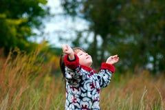 Kind, das oben zum Himmel schaut Stockfoto