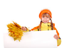 Kind, das orange Herbstblätter und -fahne anhält. Stockbilder