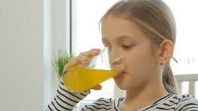Kind, das Orangensaft, Kind am Frühstück in der Küche, Mädchen-Zitrone frisch trinkt stockbild