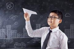 Kind, das Papierflugzeug in der Klasse spielt Lizenzfreie Stockbilder