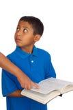 Kind, das Person beim Anhalten der Bibel betrachtet   Stockfotografie