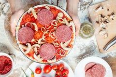 Kind, das Pizza auf hölzerner Tischplatte macht Lizenzfreies Stockfoto