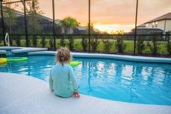 Kind, das am Rand eines Swimmingpools an einem warmen Sommertag sitzt stockbild