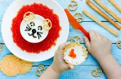 Kind, das rotes Kaviarsandwich mit Sauerrahmsoße kocht Stockbild