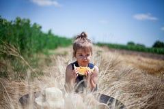 Kind, das Scheibe der gelben Wassermelone in einer Wiese isst lizenzfreies stockfoto