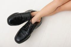 Kind, das in Schuhe des Vaters tritt Lizenzfreie Stockbilder