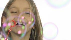 Kind, das Seifenblasen, glückliche lächelnde Mädchen-Schlagballone, Zeitlupe spielt stock footage