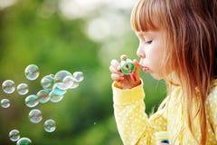 Kind, das Seifenluftblasen beginnt stockbild