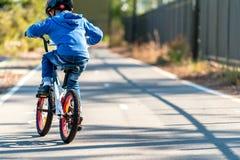Kind, das sein Fahrrad auf Radweg fährt Stockbilder