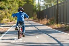 Kind, das sein Fahrrad auf Radweg fährt Stockfotos