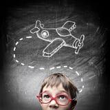 Kind, das an sein neues Spielzeug denkt Lizenzfreie Stockfotos