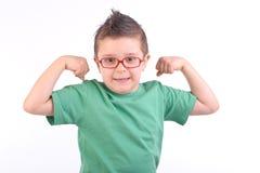 Kind, das seine Muskeln zeigt stockfotografie